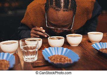 African man smelling the aroma of coffee at a tasting -...