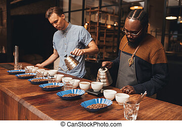 Two baristas preparing a coffee tasting in roastery -...