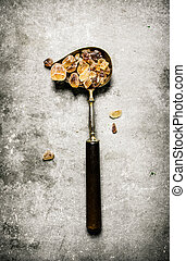 Crystal brown sugar in an old spoon. On a stone background.