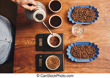 Barista pouring water into cup of ground coffee on scale -...