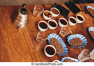 Cups of coffee, beans, and kettle on table for tasting -...