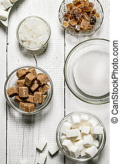 Different types of brown and white sugar in the cups.