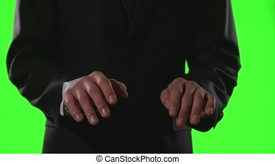 Young businessman making typing gestures in a virtual business environment on green screen