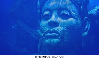 Head Of Ancient Deity Statue In Sea - Closeup of a huge...