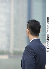 Behind view of an Asian businessman looking away - Rear view...