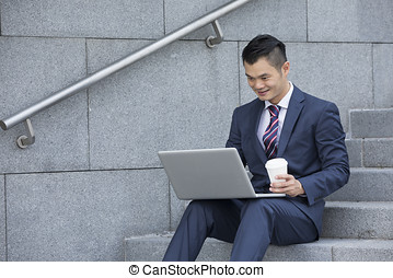 Asian business Man using his laptop outdoors - Chinese...