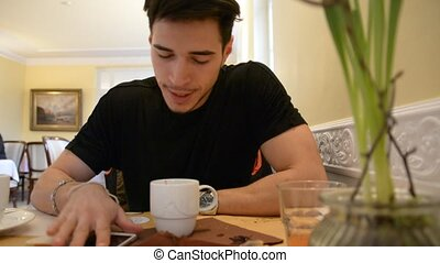 Young Man Drinking Coffee While Looking at Phone - Close up...