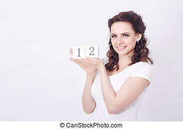 Girl in white t-shirt holding number Twelve.