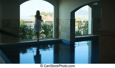 Silhouette of sexy bride in white translucent robe in hotel...