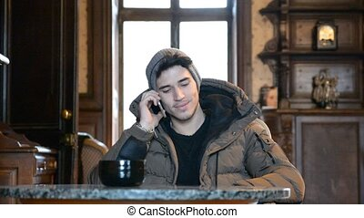 Handsome young man talking on telephone at home sitting on...