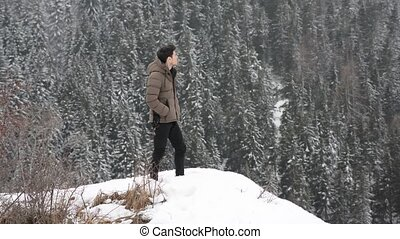 Man in outerwear standing in snow - Handsome man in...