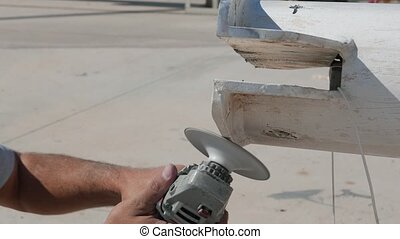 Worker sanding yachts mast with angle grinder Close up -...