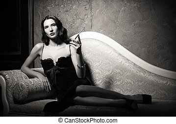 Film noir style: dangerous elegant young woman lying on sofa...