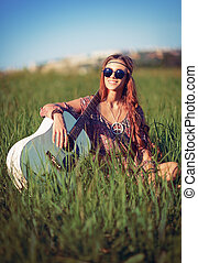 Portrait of beautiful smiling hippie woman with guitar in...