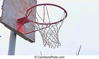 Action shot of basketball going through basketball hoop and...