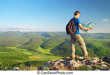 Man tourist in mountain read the map. Man on top of mountain. Tourism concept