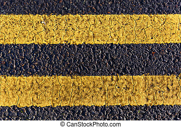 Asphalt road and painted yellow lines - Close up photo of...