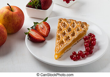 apple pie slice on white plate with fruits