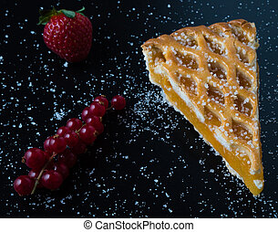 apple pie slice on black table with currant and strawberry