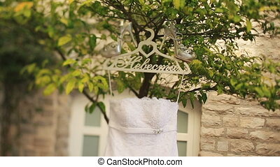 Vintage wedding dress with silver shiny heels hanging on hanger on tree branch