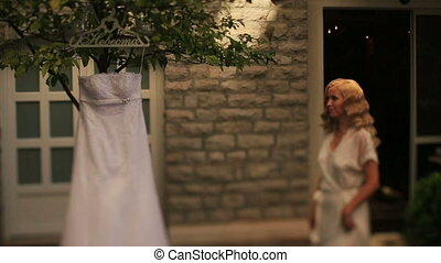 Beautiful blond bride in white robe touching her vintage...