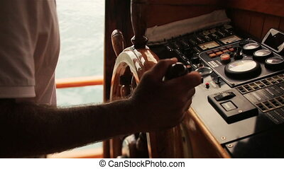 Captain keeps the wheel of his yacht close up,