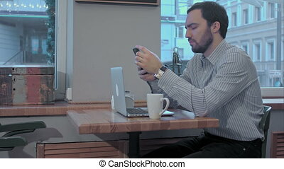 Serious businessman using mobile phone during coffee break in cafe, looking at his watch