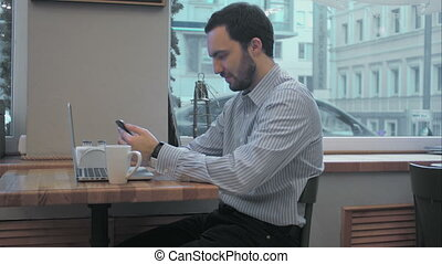 Successful young businessman using cell telephone during coffee break in cafe inside