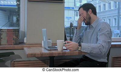 emotional freelancer man with laptop yawns early in the morning in cafe,