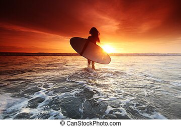 Surfer woman on beach at sunset - Beautiful surfer woman on...