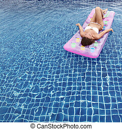 Woman relaxing in a pool floating on water bed