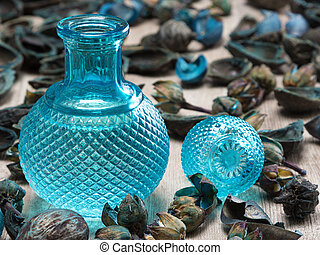 Blue glass bottle surrounded by dried plants - Close-up of...