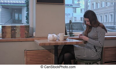 Girl texting on the smart phone in a cafe, useing internet