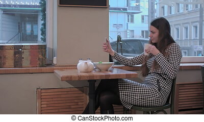 Beautiful woman making self portrait with mobile phone camera while sitting in cafe