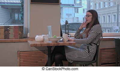 business woman in cafe talking by video conference eating...