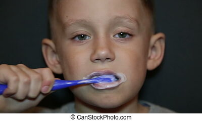 A boy brushing his teeth - little kid cleans his teeth with...