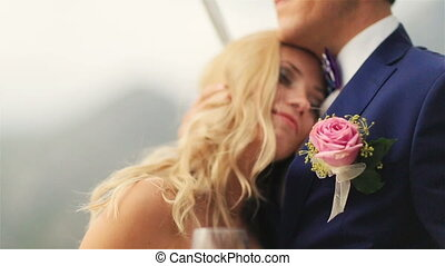 Young happy bride softly puts head on grooms chest and...