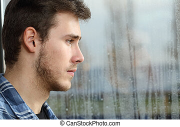Man longing and looking through window - Side view of a man...