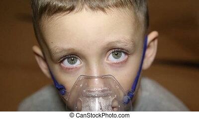 A cold boy breathes in an inhaler