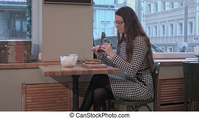 Young woman eating sandwich in the cafeteria with pleasure...