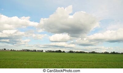 green field and blue sky with clouds in slowmotion....