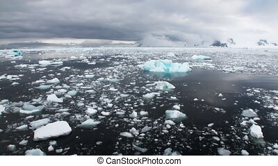 Ice and small icebergs floats on ocean surface. - Ice and...