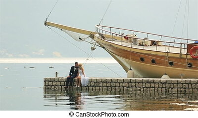 Happy wedding couple sitting on the berth, waving legs and...