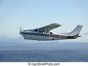 Cessna 210 light aircraft flying over Westland, New Zealand