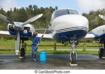 washing grandads plane - 7-year-old boy washing his...