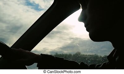 Man driving the car under sunset sky at outdoor in...