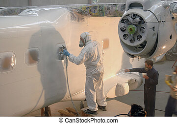 final coat - Tradesman sprays the fuselage on a Dornier 228...