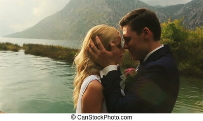 Wedding couple tenderly kissing with the sea and mountains in Montenegro, Budva on background close up