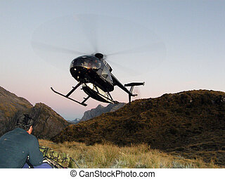 Helicopter landing on ridge top, West Coast, South Island,...