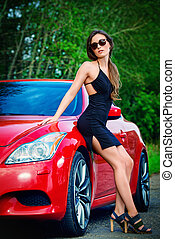 red sports car - Attractive young woman near the red sports...